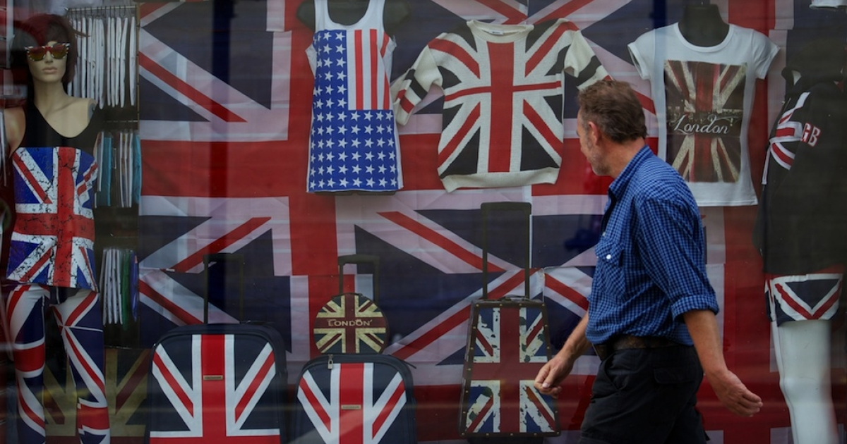 A man walks past the window of a shop selling clothing and goods bearing the Union Flag in London on August 7, 2013.</p>