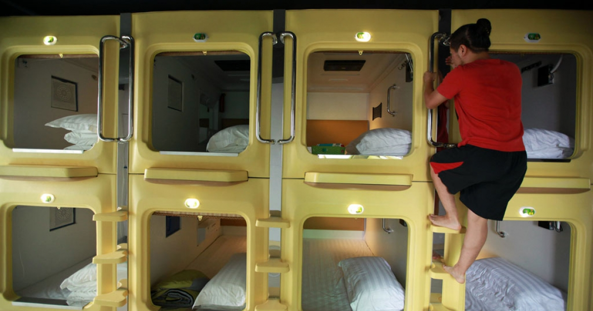 A guest climbs down a capsule in a newly opened capsule hotel in Haikou, south China's Hainan province on Aug. 13, 2013.</p>