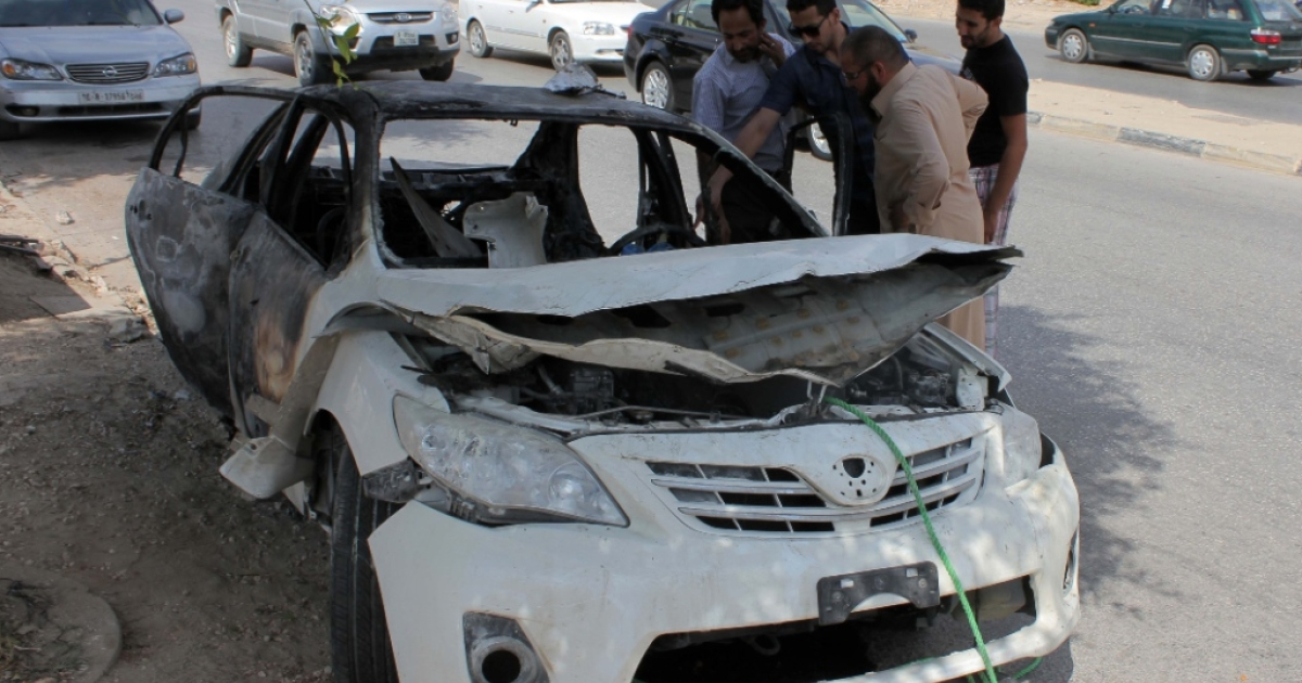 Libyan men inspect the wreckage of a car on August 6, 2013 in the eastern Mediterranean city of Benghazi. A bomb exploded under a car in Benghazi killing the driver, a security official told AFP, the latest in a wave of violence to hit the restive city.</p>