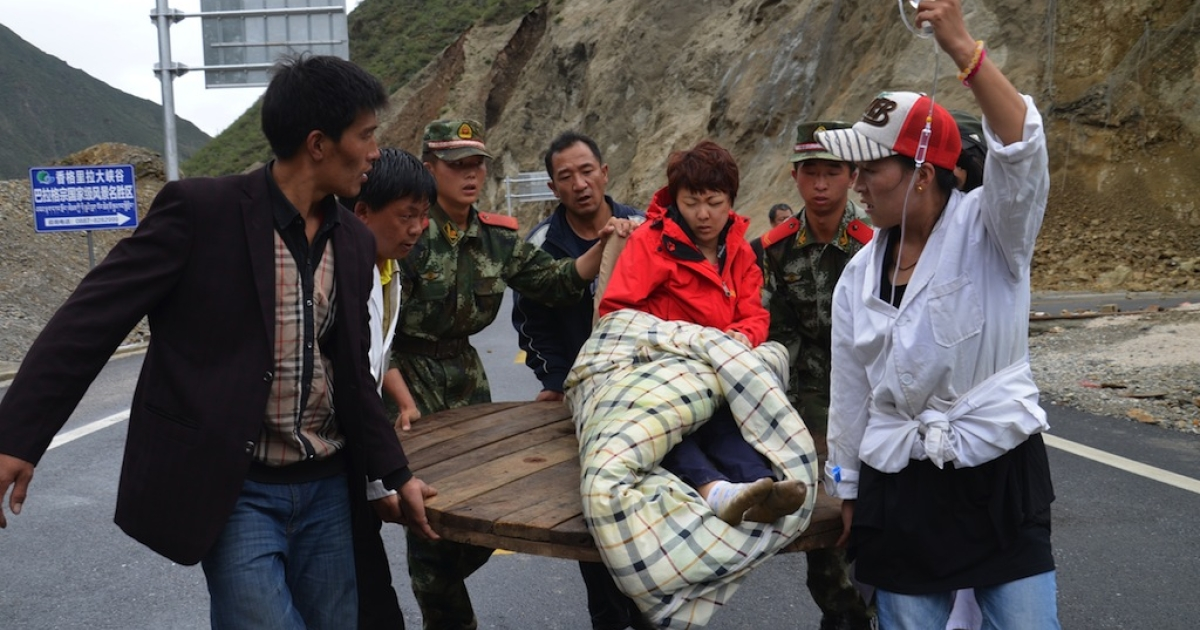 Rescuers and local residents help an injured woman (C) following an earthquake in Deqin county, southwest China's Yunnan province on August 31, 2013. An earthquake on August 31 hit a remote part of southwest China near the popular tourist area of Shangri-La, killing four people and injuring over a dozen more, state media said.</p>