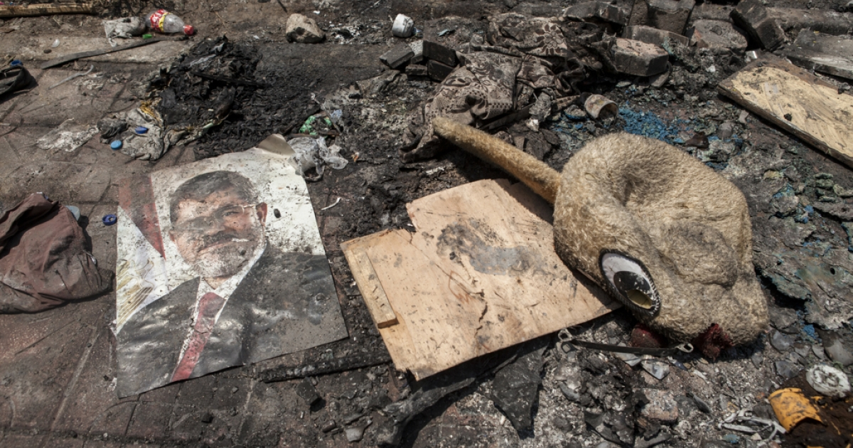 A poster of deposed Egyptian President Mohammed Morsi lies in the debris left outside the Rabaa al-Adaweya Mosque in Nasr City on August 15, 2013 in Cairo, Egypt. An unknown number of pro-Morsi protesters were killed in Egypt's capital on Wednesday as Egyptian security forces undertook a planned operation to clear Morsi supporters from two sit-in demonstrations in Cairo.</p>