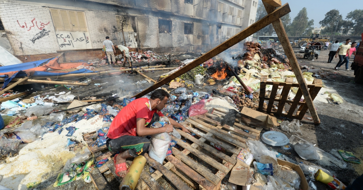 An Egyptian garbage collector inspects the remains of the destroyed camp of ousted Mohammed Morsi supporters outside Rabaa al-Adawiya mosque on August 15, 2013 in Cairo, Egypt.</p>