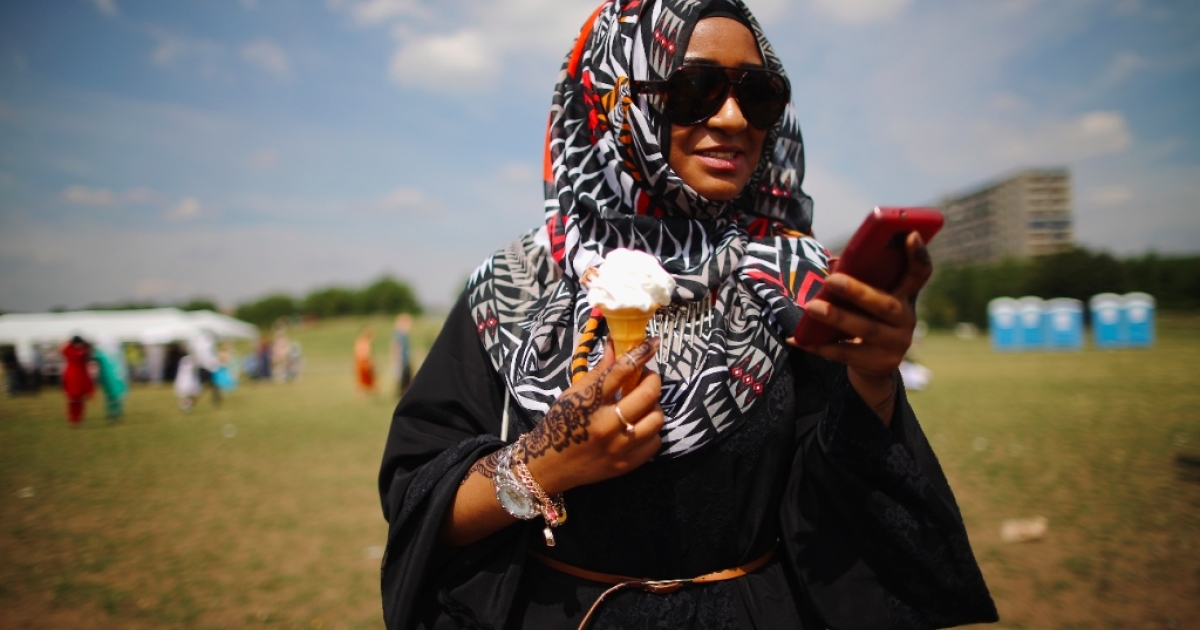 Muslim woman enjoys an ice-cream during an Eid celebration fun fair in Burgess Park on August 8, 2013 in London, England. The Muslim holiday Eid marks the end of 30 days of dawn-to-sunset fasting during the holy month of Ramadan.</p>
