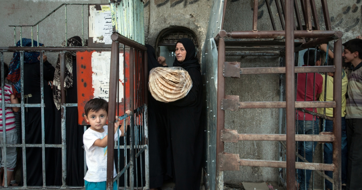 A Syrian woman carrying a bag of bread exits a bakery run by the Islamic rebel group