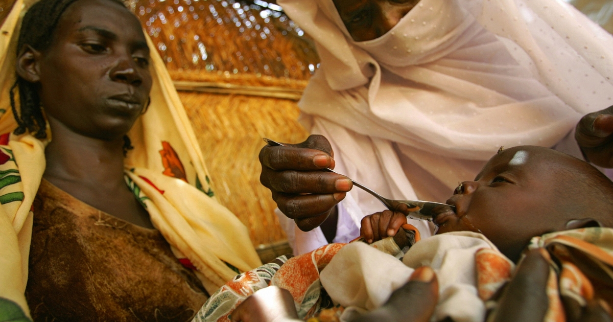 A Sudanese mother holds her 12 day-old baby on her lap as a nurse feeds him medicine to fight diarrhea and dehydration 16 September 2004 at a Save the Children/US Aid Clinic in the Internally Displaced Persons camp of Krinding on the outskirts of the western town of El-Geneina.</p>
