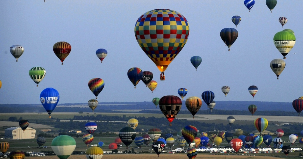 Hot air-balloons fly over a field of sunflowers in Chambley-Bussieres, eastern France on July 27, 2013 as part of the yearly event 'Lorraine Mondial Air Balloons,' an international air-balloon meeting.</p>