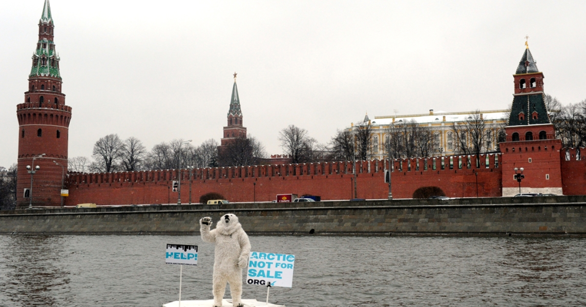 Wearing a costume of polar bear a Greenpeace activist takes part in a staged show on the Moskva River in front of the Kremlin in Moscow on April 1, 2013.</p>