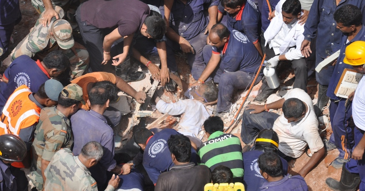 Indian rescue personnel administer oxygen to an injured man (C) trapped in the debris of a collapsed residential building near Vadodara, some 110 kms from Ahmedabad, on August 28, 2013. Eleven residents were killed and another four injured and when the three-story residential building collapsed during pre-dawn hours.</p>