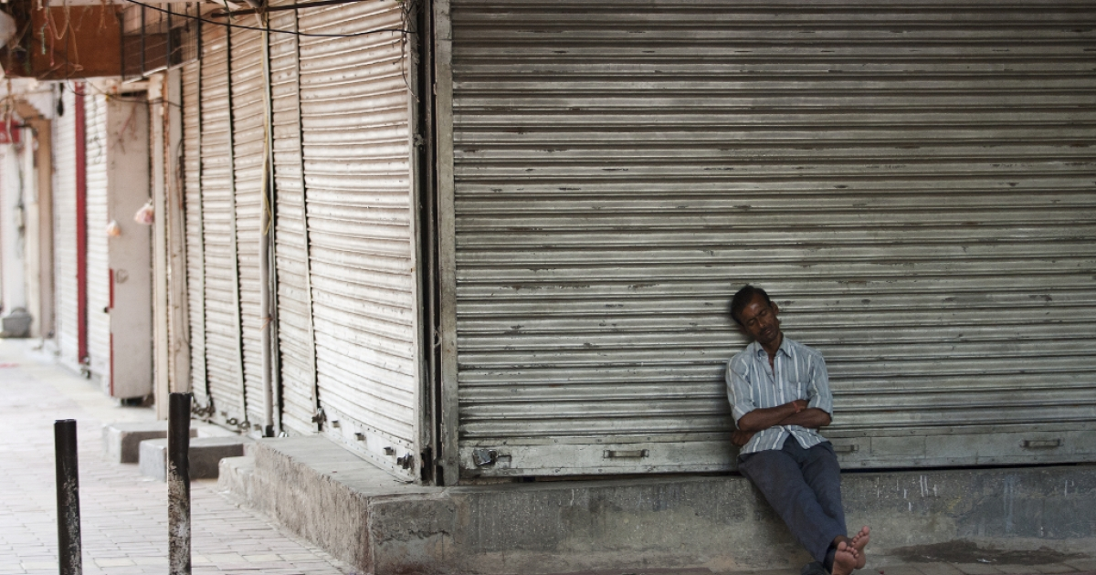 A man sleeps in front of a closed business. Billions of dollars of foreign investment is leaving India, the government is scrambling to rein it in.</p>
