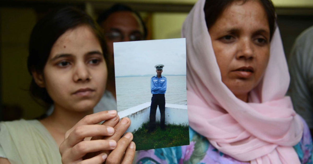 Suman Sharma shows a photograph of her son, Atul, as her daughter Rashmi looks on in Amritsar, India, on Aug. 16, 2013. Atul is one of 18 missing sailors presumed dead after a submarine exploded in a Mumbai dockyard days earlier.</p>