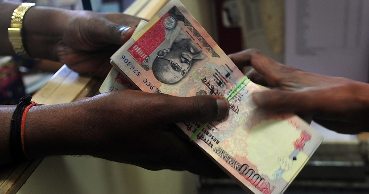 A customer receives a wad of Indian rupee notes from a foreign exchange dealer in Mumbai on August 6, 2013.</p>