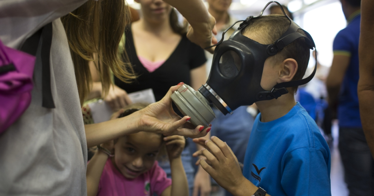 An Israeli woman shows her children how to put on a gas mask as they pick their gas masks at a distribution center on August 26, 2013 in Tel Aviv, Israel. Israel keeps distributing gas masks to its civilian population as tension rises in Israel amid international talks of a military intervension In Syria.</p>