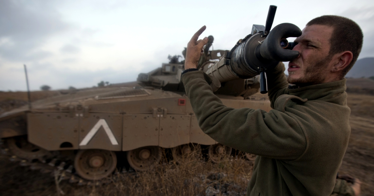 An Israeli soldier checks a Merkava tank during a military exercise in the Israeli-annexed Golan Heights near the border with Syria on July 18, 2013.</p>
