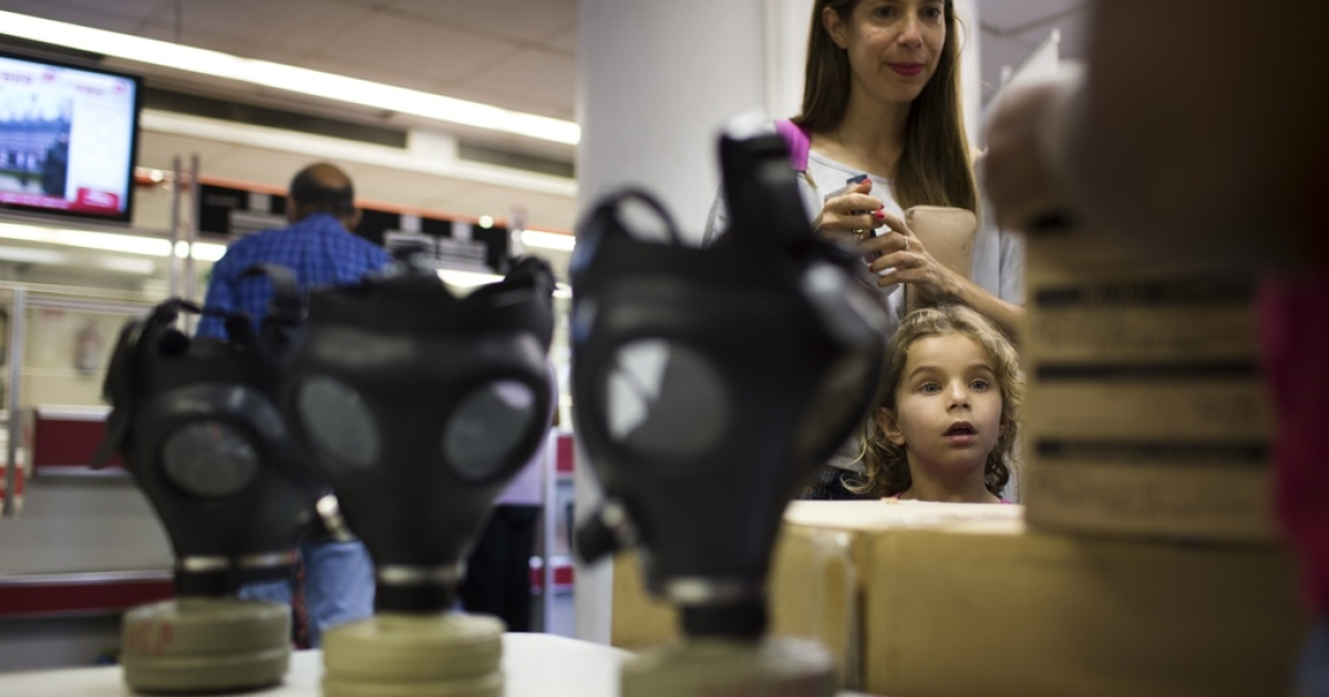 Israelis wait in line to pick their gas masks at a distribution center on Aug. 26, 2013 in Tel Aviv, Israel.</p>