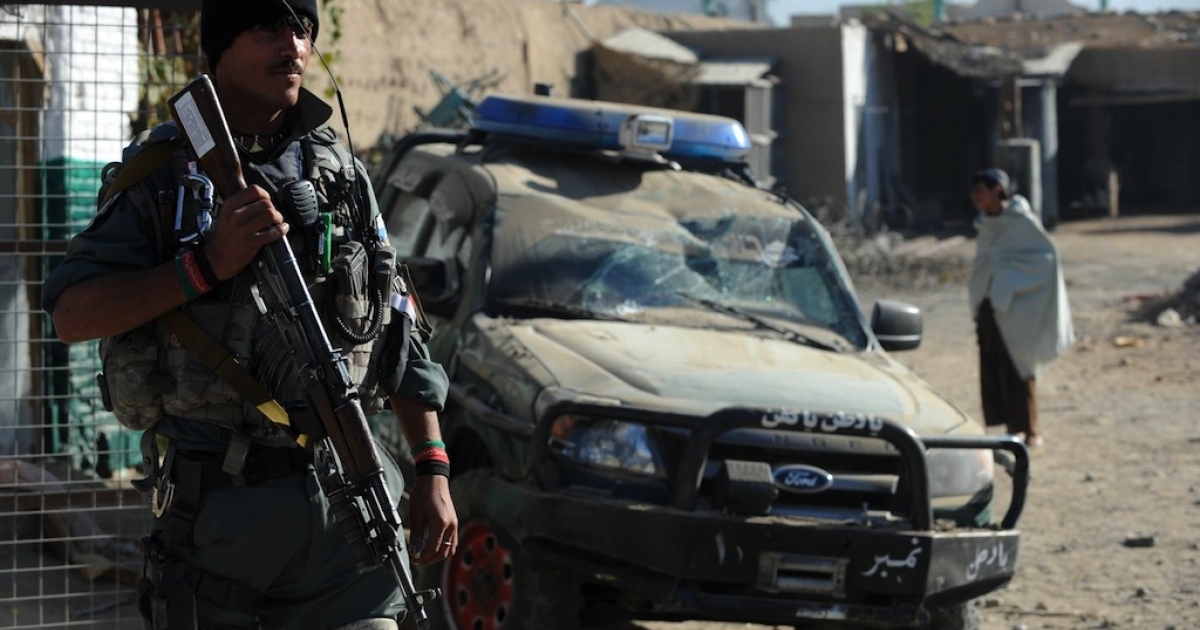An Afghan policeman keeps watch at the site of a suicide bomb attack in Kandahar on Nov. 8, 2012.</p>