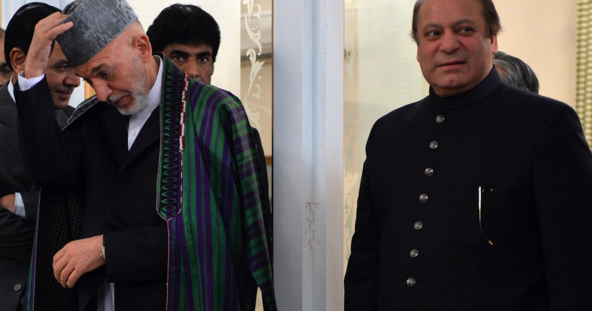 Visiting Afghan President Hamid Karzai (L) adjusts his cap as he arrives with Pakistani Prime Minister Nawaz Sharif (R) for a press conference at The Prime Minister's House in Islamabad on Aug. 26, 2013.</p>