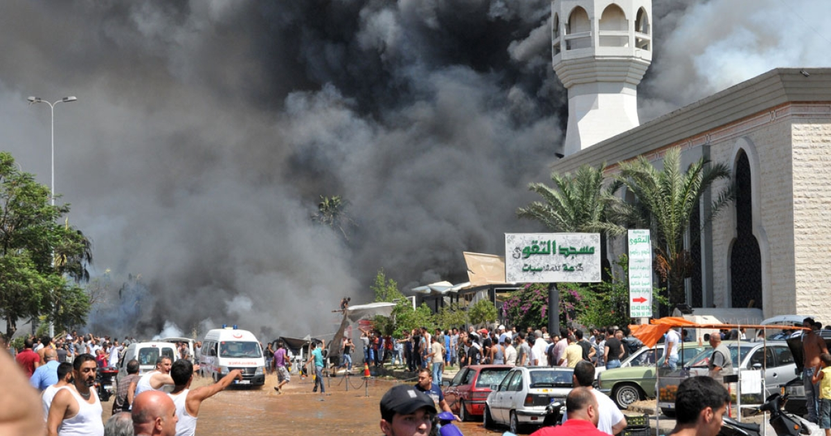 Smoke rises outside a mosque at the site of a powerful explosion in Tripoli, Lebanon, on August 23, 2013. Two powerful explosions killed several people: one rocked the city center near the home of outgoing Prime Minister Najib Mikati, and the second one struck near the port of the restive city with a Sunni Muslim majority.</p>