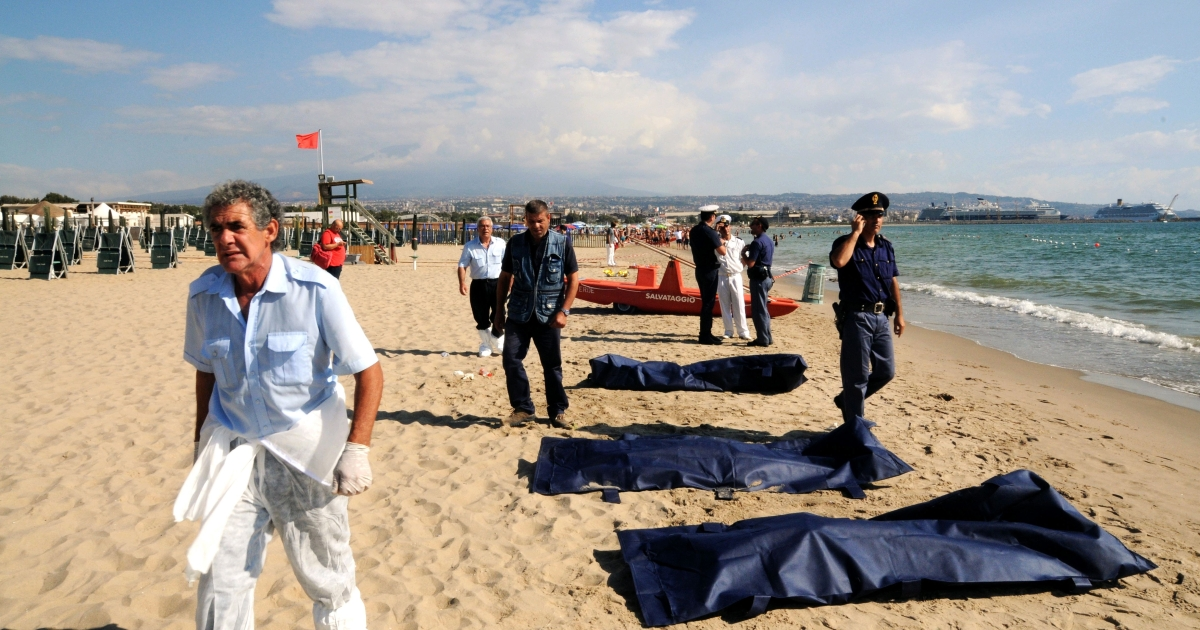 Police and rescuers stand by the bodies of immigrants on a beach of the Sicilian city of Catania on Aug. 10, 2013. The bodies of six migrants from Africa were found on the beach while nearly 100 others, thought to be Syrians and some Egyptians, were rescued in the latest desperate attempt to reach Europe.</p>