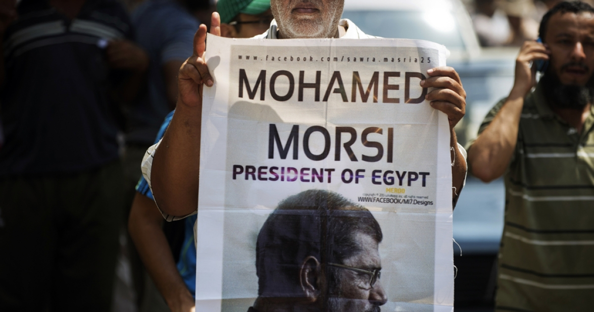 A man holds a portrait of ousted president Mohamed Morsi. Morsi's Muslim Brotherhood may lose its status as an NGO as the military crackdown of the group continues.</p>
