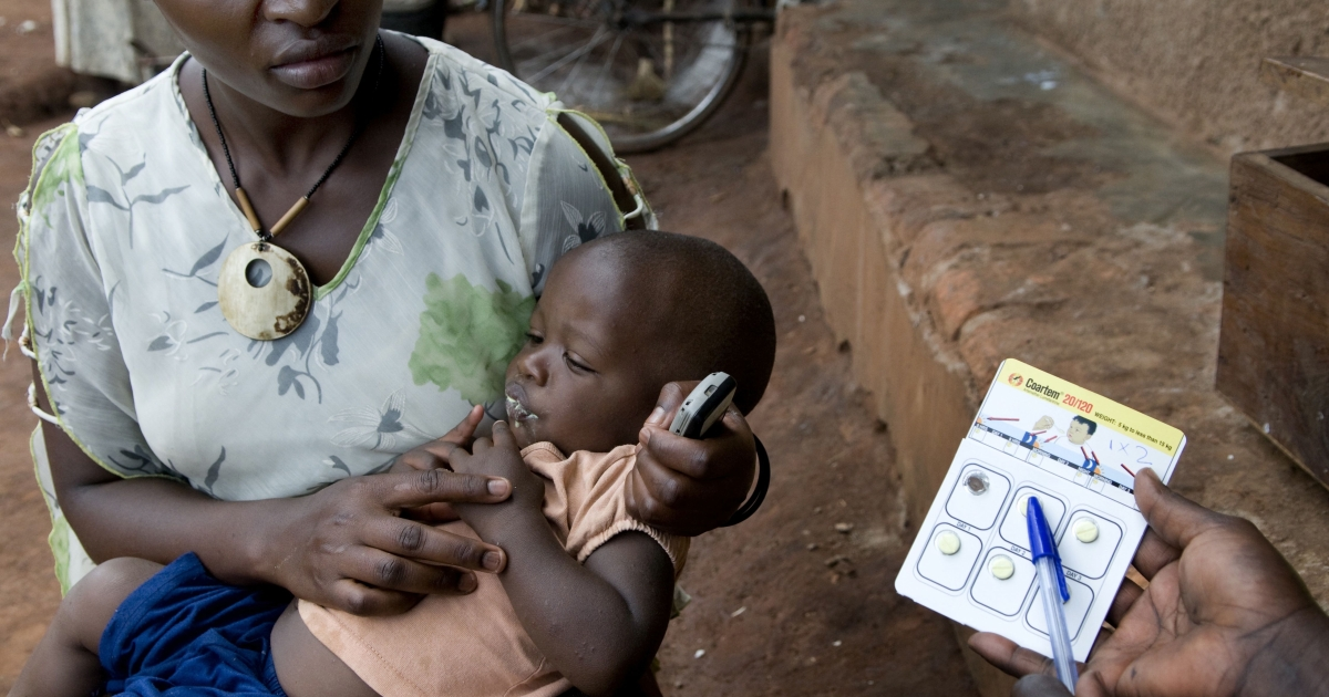 A community medicine distributor explains how to use anti-malaria medicine to Carolyn Nampera, mother of Elijah Bumba, 14 months, in her house in Kiboga District, Uganda.</p>