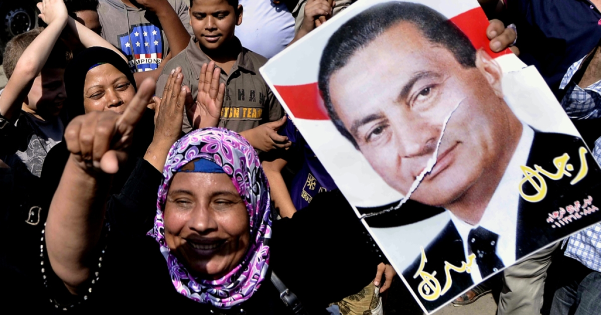 An Egyptian supporter of former Egyptian president Hosni Mubarak raises up his portrait outside the Tora prison where Mubarak is detained, on August 22, 2013 in Cairo, Egypt. Egypt's toppled dictator Hosni Mubarak is expected to leave jail after a court ordered him released pending trial, but he will immediately be placed under house arrest.</p>