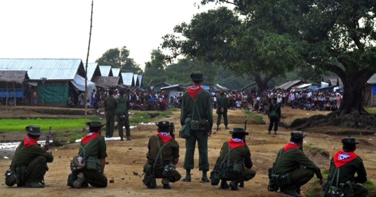 Myanmar security force personnel stand guard while a mob (background) look on following unrest at an Internally Displaced People (IDP) camp for Muslim Rohingyas on the outskirts of Sittwe town in Rakhine State on August 9, 2013.  The United Nations has called for dialogue after another violent clash in a camp for dispossessed Rohingya Muslims in western Myanmar, as its human rights envoy toured the strife-torn area.</p>