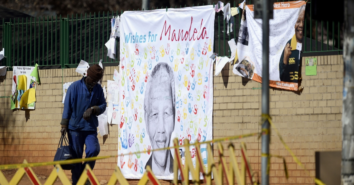 A worker passes nearby a banner with well-wishing messages left for former South African President Nelson Mandela on July 19, 2013, outside the Medi Clinic Heart Hospital in Pretoria.</p>
