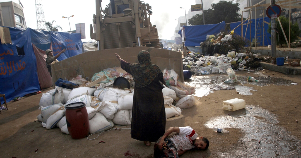 An Egyptian woman tries to stop a military bulldozer from hurting a wounded youth during clashes that broke out as Egyptian security forces moved in to disperse supporters of Egypt's deposed president Mohamed Morsi in a huge protest camp near Rabaa al-Adawiya mosque in eastern Cairo on August 14, 2013.</p>