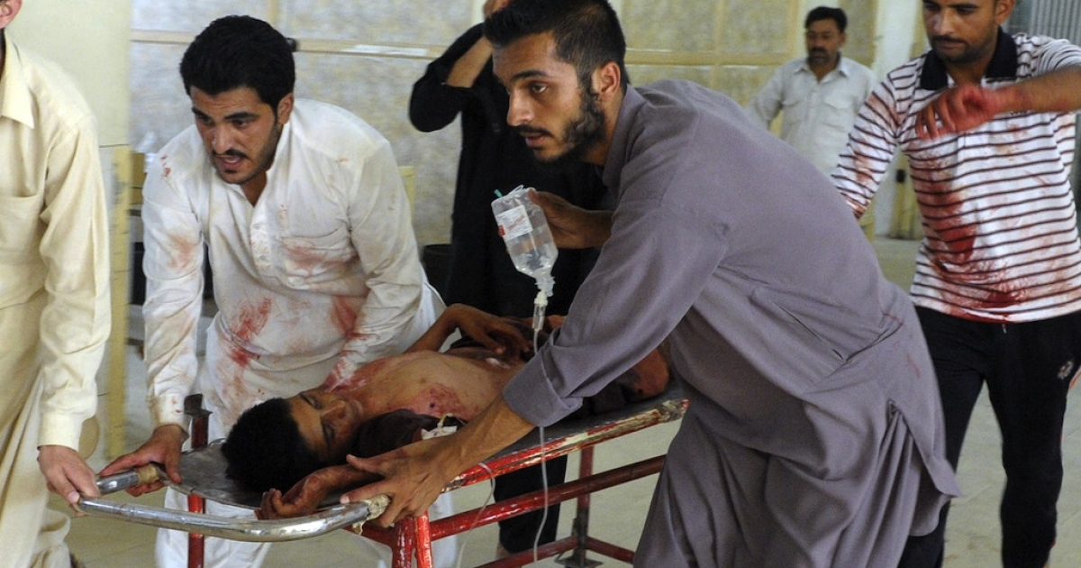 Pakistani men carry an injured blast victim at a hospital in Quetta on August 8, 2013, following a suicide bomb attack at a policeman's funeral.</p>