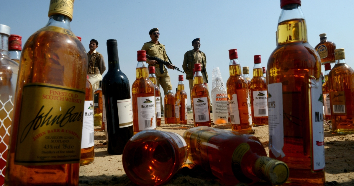 Pakistani customs officials are pictured behind bottles of alcohol before their destruction on the outskirts of Karachi on Jan. 26, 2013.</p>