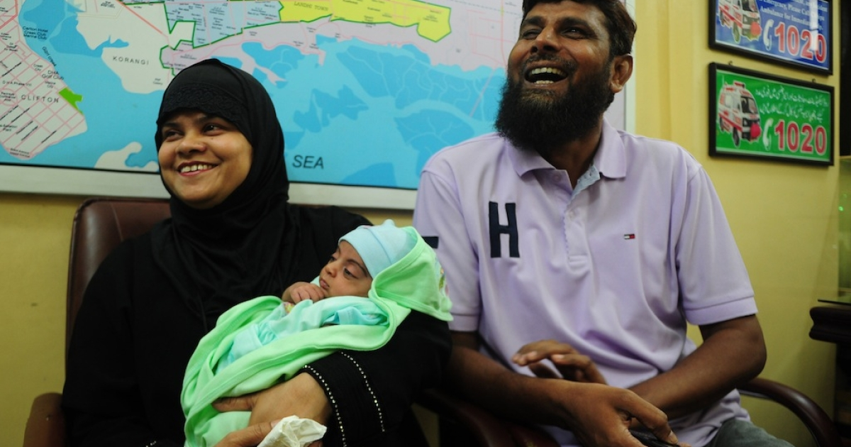 Pakistani couple Riazuddin (R) and his and wife Tanzeem laugh as they hold their adopted daughter Fatima at The Chhipa Welfare Association in Karachi on Aug. 1, 2013.</p>