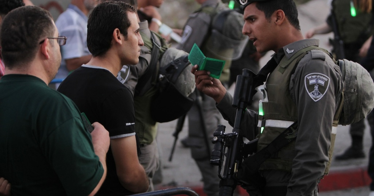An Israeli soldier checks the ID of a Palestinian man people walk through Israel's Qalandia checkpoint between Ramallah and Jerusalem, in the occupied West Bank, on Aug. 4, 2013.</p>