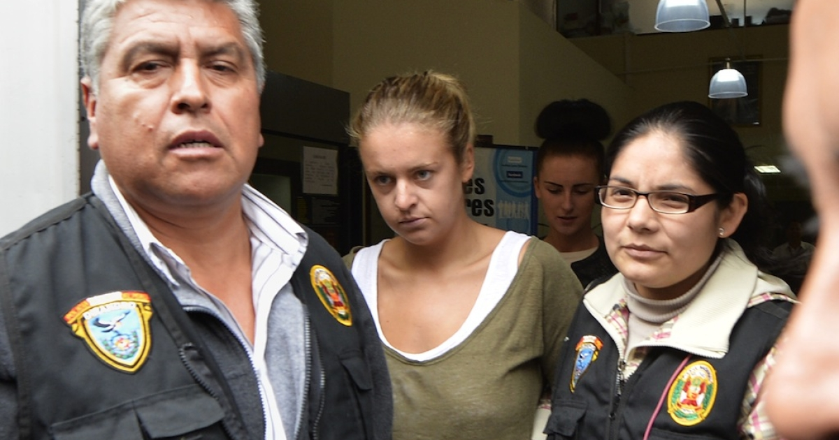 Melissa Reid (C), a British woman arrested on August 6, 2013 at Lima's airport carrying cocaine in her luggage is escorted out of the Callao prosecutors building on August 20, 2013, to be taken to the district court with her companion Michaella McCollum, 20, (background)..</p>