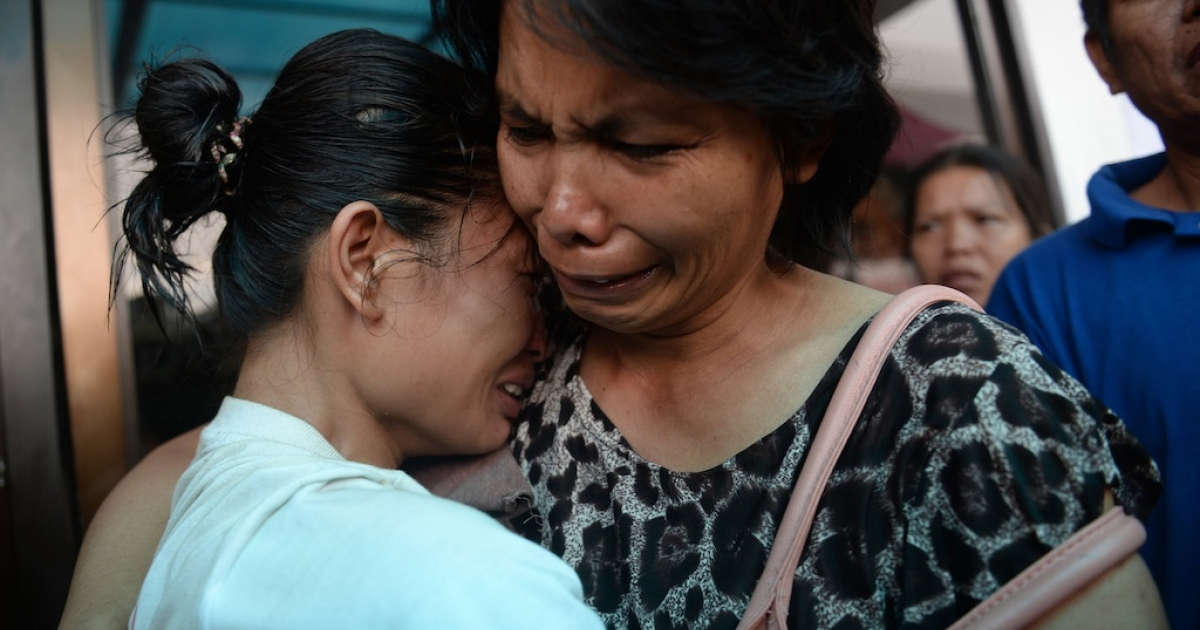 A survivor (L) reacts as she is reunited with a relative outside the ferry company's office in Cebu on August 17, 2013.</p>