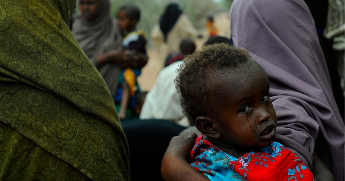 A young Somali refugee waits with her mother to be vaccinated at a pediatric vaccination centre at Hagadere refugee site within the Dadaab refugee complex in Kenya's north-east province on August 1, 2011.</p>