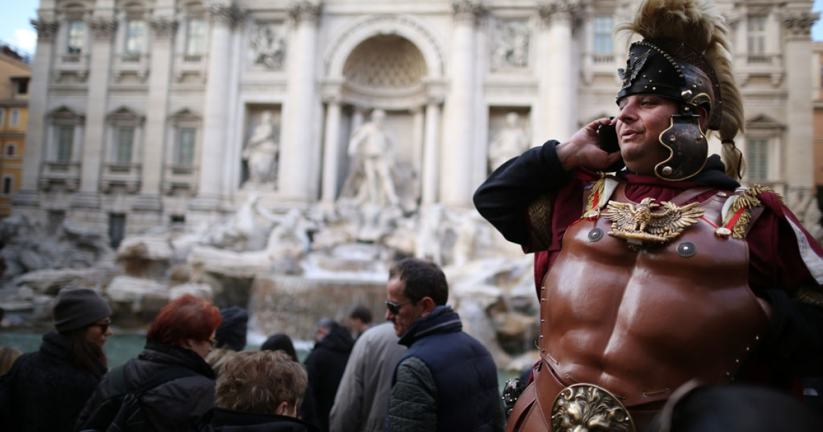 A tourist guide talks on a cellphone at the Trevi Fountain on March 16, 2013 in Rome, Italy.</p>