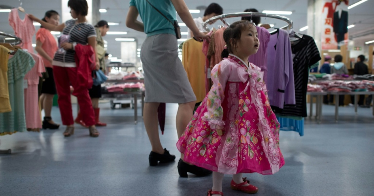 A North Korean girl wearing traditional dress stands at a clothing section inside a high-end supermarket in Pyongyang on July 28, 2013.</p>