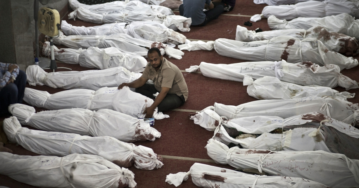 Egyptians mourn over bodies wrapped in shrouds at a mosque in Cairo on August 15, 2013, following a crackdown on the protest camps of supporters of ousted Islamist president Mohamed Morsi the previous day.</p>