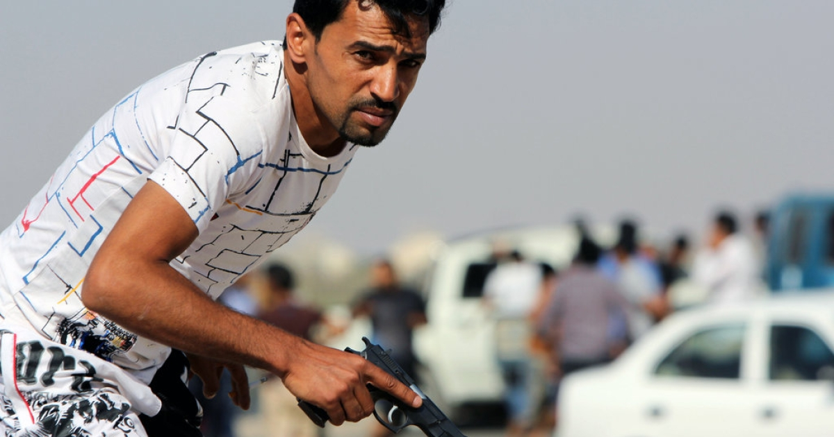 A Libyan protester holds a gun during clashes between demonstrators and troops of the Libyan Shield Forces (LSF), a coalition of militias, following a demonstration outside the LSF office in the northern city of Benghazi on June 8, 2013.</p>