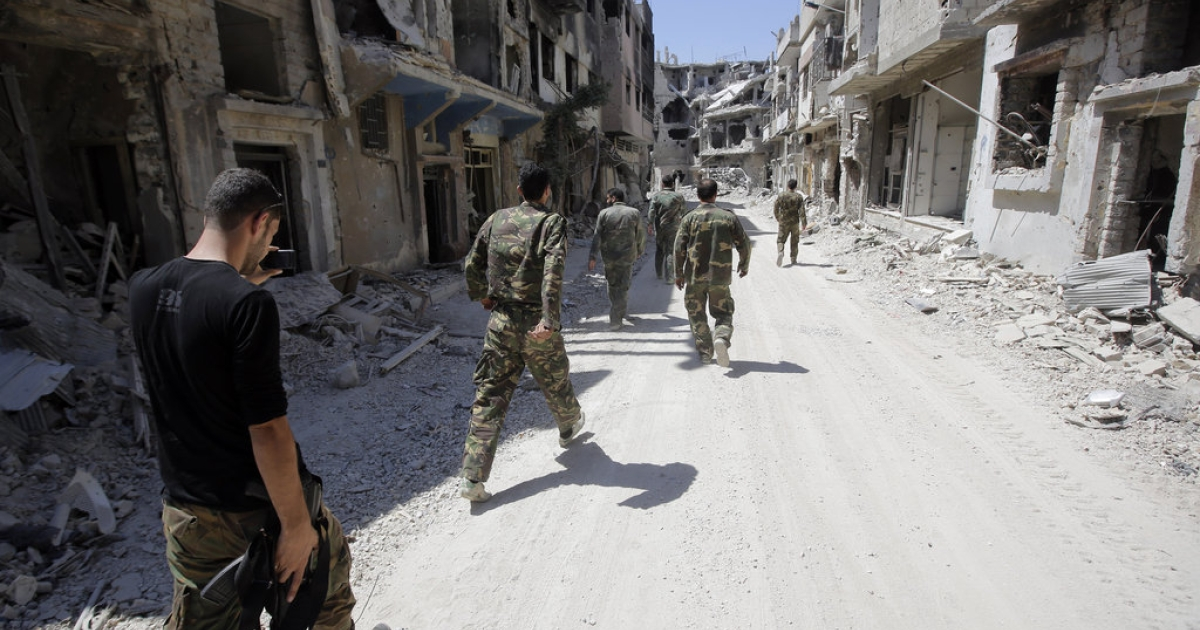 Soldiers of the Syrian government forces patrol in a devastated street on July 31, 2013 in the district of al-Khalidiyah in the central Syrian city of Homs. The Syrian government announced the capture of Khalidiyah, a key rebel district in Homs, Syria's third city and a symbol of the revolt against President Bashar al-Assad.</p>