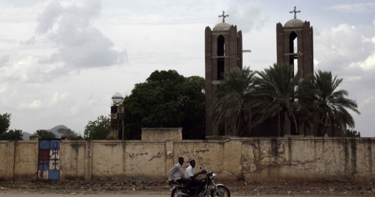 Two Sudanese youths ride their motorcycle past a church in Kadugli, the capital of Sudan's war-torn South Kordofan state, on June 19, 2013. Insurgents from the Sudan People's Liberation Army-North, fighting since 2011 in South Kordofan, have since last year periodically shelled Kadugli.</p>