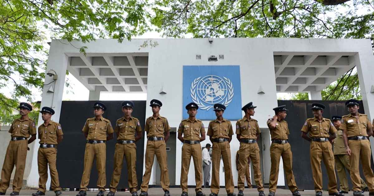 Sri Lankan police officials stand guard outside the United Nations office in Colombo on Aug. 26, 2013, during a demonstration by 'Power of Ravana' Buddhist monks denouncing UN human rights chief Navi Pillay on the first full day of her visit to Sri Lanka.</p>