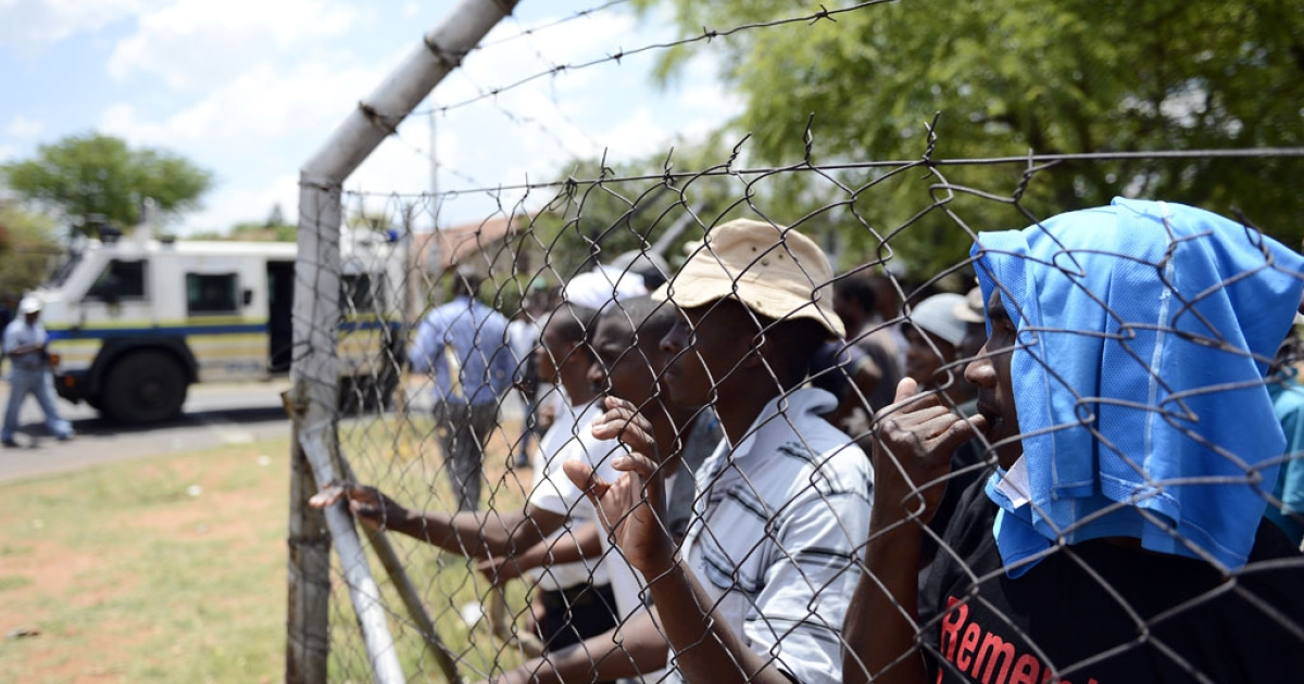 Striking miners look through a fence at riot police at a rally organized by the Congress of South African Trade Unions in Rustenburg, northwest of Johannesburg, on October 27, 2012. South African gold mines are again bracing for strikes, officials said on Aug. 28, 2013.</p>