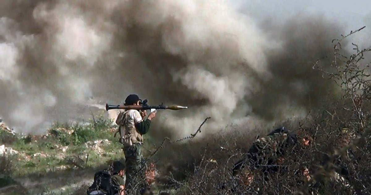 An image grab taken from a video shows opposition fighter holding a rocket propelled grenade (RPG) as his fellow comrades take cover from an attack by regime forces on August 26, 2013 during clashes over the strategic area of Khanasser, situated on the only road linking Aleppo to central Syria.</p>