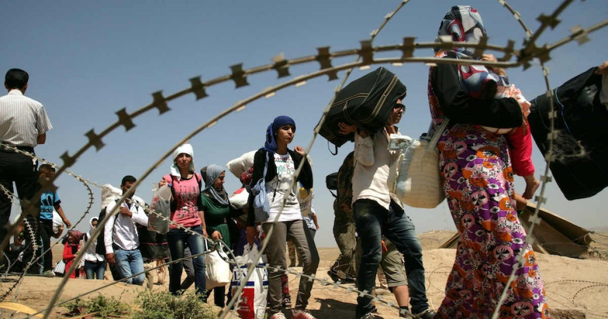 Syrian refugees cross the border into the autonomous Kurdish region of northern Iraq, on Aug. 18, 2013.</p>