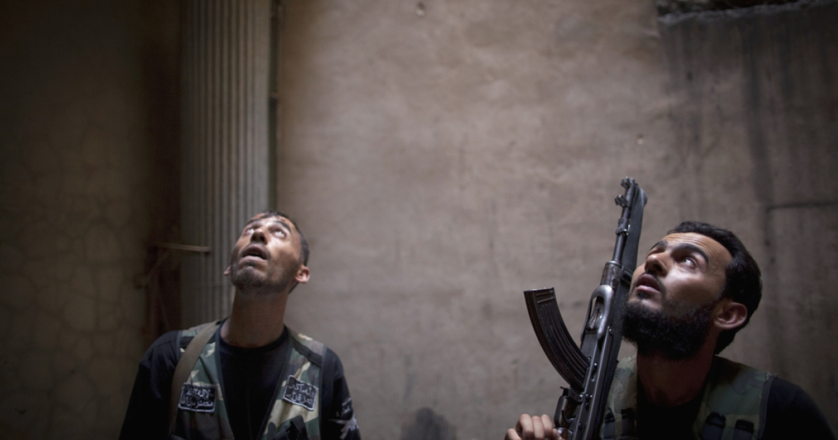 Rebel fighters look up listening as they take positions during clashes with pro-government forces in the Salaheddine district of the northern Syrian city of Aleppo, on July 9, 2013.</p>