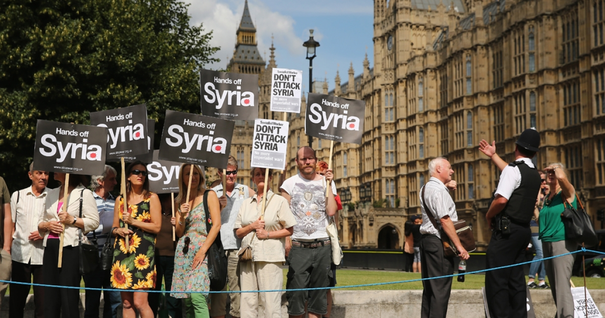 Anti-war protesters gather on College Green outside the Houses of Parliament on Aug. 29, in London, England. Lawmakers there voted against plans for a UK military response to chemical weapons attack in Syria.</p>