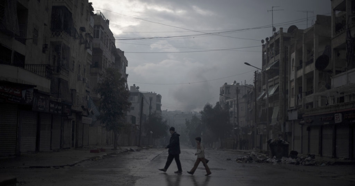 A father and son return home with vegetables, as smoke from a pro-government forces artillery strike ascends in the background, in the al-Amaria neighborhood in the city of Aleppo, on Jan. 6, 2013.</p>