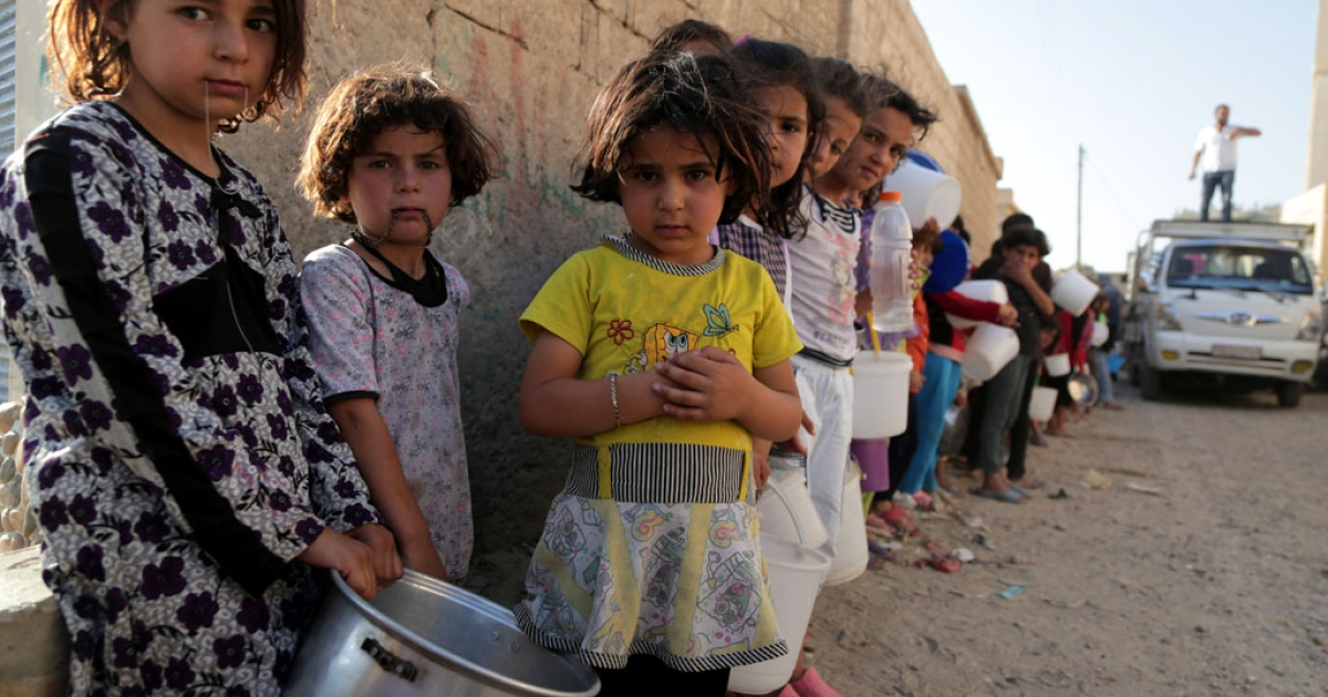 Syrian children wait in line to collect a free Iftar meal in the northern city of Raqqa during the Muslim holy month of Ramadan on July 14, 2013.</p>