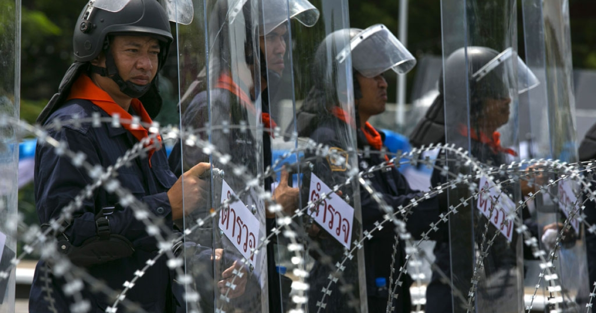 Thai riot police stand guard near Parliament during an anti-government protest on August 7, 2013 in Bangkok. Opposition to Yingluck Shinawatra's government gathered to protest against an amnesty bill.</p>